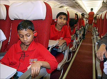 Kids sit in a Kingfisher aircraft.