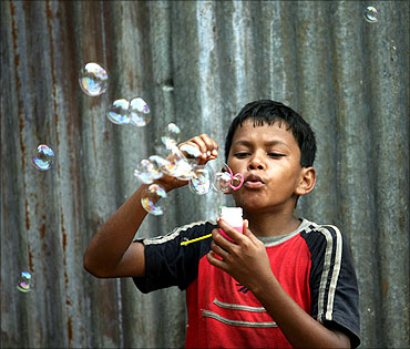 A boy selling bubble-making toys, blows bubbles to attract buyers in Mumbai.
