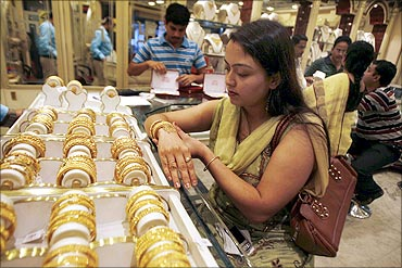 A woman tries on a gold bracelet at a jewellery showroom in Siliguri.