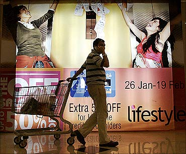 An Indian pulls his trolley as he passes by an advertising display at a shopping mall in Mumbai.