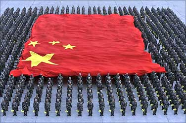Paramilitary police officers hold a Chinese national flag during a parade training session.