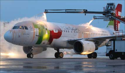 A TAP Portugal plane is being de-iced.