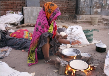 A homeless woman prepares food on a roadside in Ahmedabad.