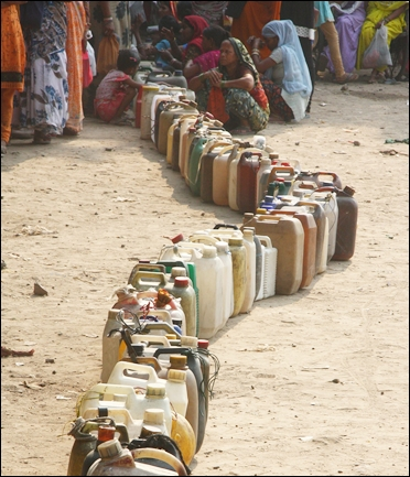 People wait with cans to collect kerosene from the ration shop.