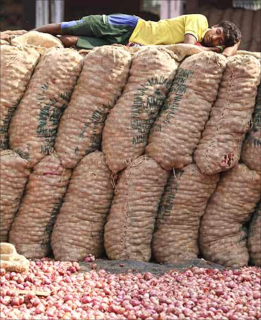 A labourer takes a nap on sacks of onions at a wholesale vegetable market.