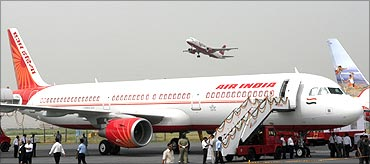 An Air India Airbus A321 sits on the tarmac as a Kingfisher Airlines aircraft takes off.