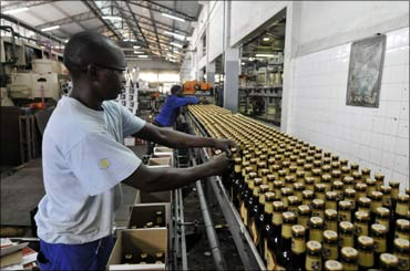 Workers package beer at Cervejas de Mocambique, a subsidiary of giant SAB Miller, in Maputo, Mozambique.