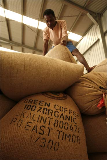 An East Timorese worker moves a sack of coffee at a warehouse outside Dili.