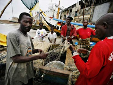 Local fishermen mend their nets in front of Cape Coast Castle, a former slave holding facility, in the Ghanaian town of Cape Coast.