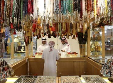 A salesperson shows chaplets to shoppers at Villagio Mall, a popular shopping area in Doha, Qatar.