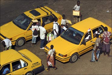 Street vendors mob taxi cabs with their wares as they come to a stop in traffic in Monrovia, Liberia.