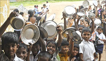 School children hold their plates as they wait for their free lunch at a government primary school.