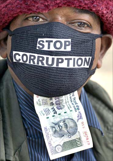 An employee of telecom operator systems, displays an Indian currency note as he takes part in a silent protest against the telecom corruption scandal.