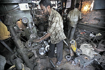 Workers make spare parts for containers at a workshop on the outskirts of Mumbai.
