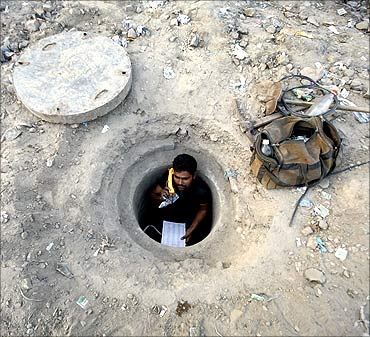Munna Yadav, 35, speaks on a phone after repairing underground telephone cables at Noida.