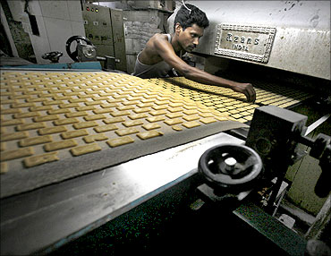 A worker sorts out damaged biscuits at a factory in Kolkata.