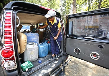 An employee fills up containers with petrol at a pump station.