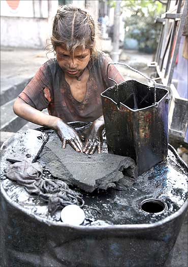 Gudia, an oil scavenger, collects engine oil at an auto workshop in Jammu.