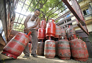 A worker arranges cooking gas cylinders in a truck outside a shop in Mumbai.