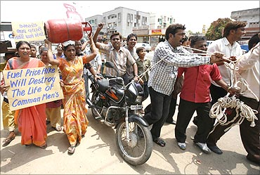 A woman carries a cooking gas cylinder as men pull a string tied to a motorbike during a protest.