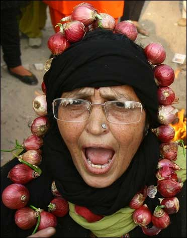 An activist from India's main opposition BJP, wearing a garland made with onions, shouts slogans.