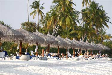 Tourists enjoy the sandy beach of Olhuveli island in Maldives.