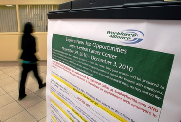 A job seeker walks past a sign at the Workforce Alliance Career Center in West Palm Beach.