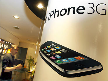 An advertisement for the Apple iPhone is shown at a retail store.