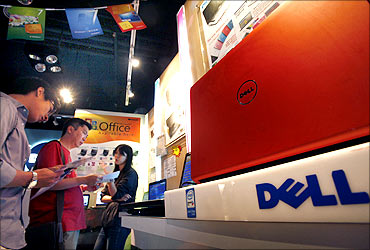 Customers examine Dell laptop models at a Dell outlet in Hong Kong.