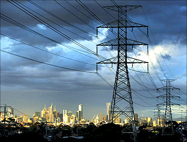 High voltage electrical transmission towers are seen near a freeway in Melbourne.