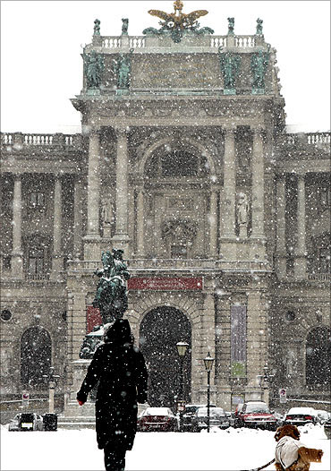 A woman with a dog walks over Heldenplatz square in front of the historic Hofburg palace.