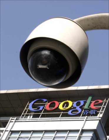 Google logo is seen on the top of its China headquarters building behind a road surveillance camera.