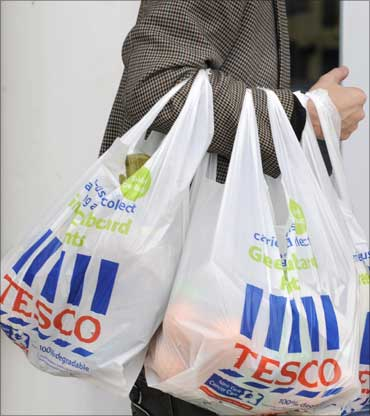 A shopper carries Tesco bags outside a branch of the supermarket, in west London.