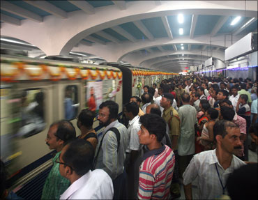 Passengers stand on a platform at a metro station in Kolkata.