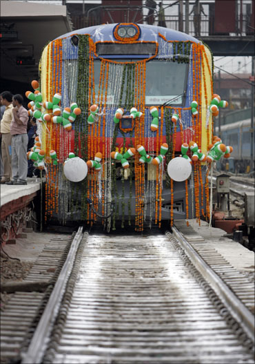 People stand near a decorated women's train before its flag-off ceremony by Railways Minister Mamata Banerjee.