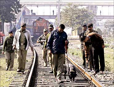 Security personnel with a sniffer dog inspect railway tracks.