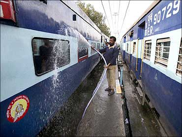 Railway employees wash a passenger train at a railway station in Jammu.