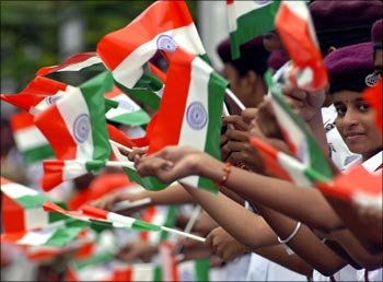 Image: Schoolchildren waving the Indian flag. Photograph: Reuters