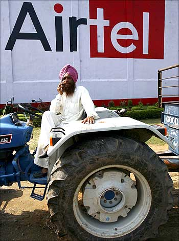 A tractor driver talks on a mobile phone in front of an advisement of Bharti Airtel.