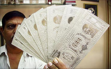 A jeweller displays silver plates in the form of Indian rupee notes in Chandigarh.