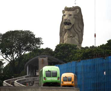 Monorail vehicles pass in front of the Merlion statue on Singapore's Sentosa Island.