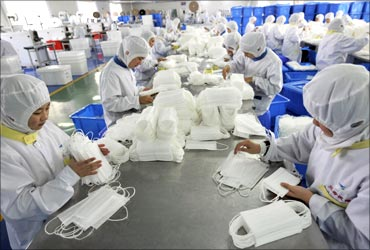 Employees pack newly made face masks at a factory in Rizhao, Shandong province.
