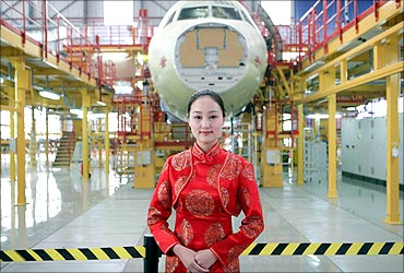 A staff member stands in front of the new Airbus A320 assembly line at its plant in Tianjin.
