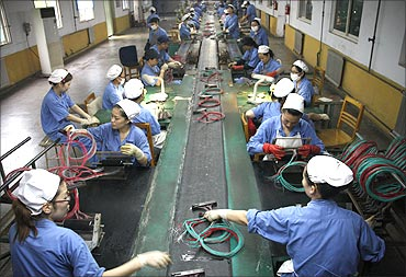 Employees make fuses at a dynamite production line of a chemical plant in Huaibei, Anhui province.