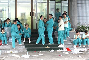 Workers stage a sit-in protest at the main entrance of Tianjin Mitsumi Electric Co. near Beijing.