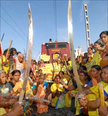 Activists from the Rashtriya Mahila Brigade (National Women's Brigade) hold swords and sticks as they block a railway track during Bharat bandh in Patna.
