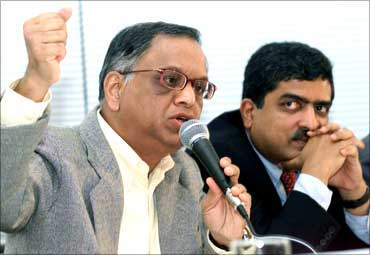 N R Narayana Murthy gestures (L) as Nandan Nilekani, looks on.