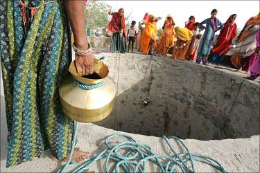 Women drawing water from the well.