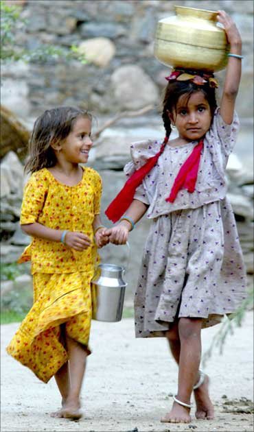 Two village girls carry home water.