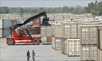 Workers walk beside the stacked containers at Sanand.